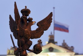 A sculpture of a double-headed eagle, a national symbol of Russia, is seen in front of a Russian national flag flying at half-mast on the roof of the State Hermitage Museum in St. Petersburg