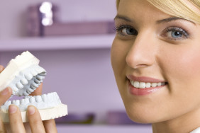 Dentist female showing reproduction model teeth and smiling