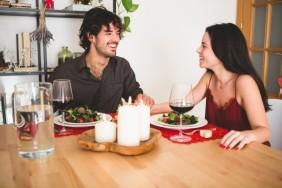 casal-sentado-a-uma-mesa-para-comer-sorrindo_23-2147596058