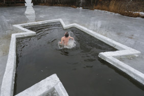 epaselect epa04568846 An Orthodox believer bathes in cold water during Epiphany celebrations in Kiev, Ukraine, 19 January 2015. During Epiphany, some people believe that the waters have special curative properties and can be used to treat various illnesses, and many of them take icy baths as part of its celebration.  EPA/SERGEY DOLZHENKO