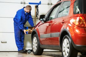 car mechanic inspecting headlight lamp of automobile at repair service station