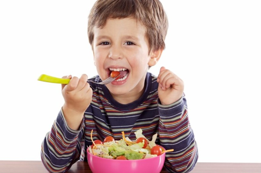 Child eating salad a over white background