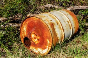 Closeup of old rusty barrel of fuel on a sunny day in the forest. Environmental pollution concept.