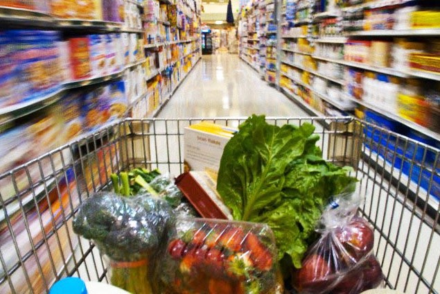 Grocery cart going down supermarket aisle --- Image by © Roy Morsch/Corbis
