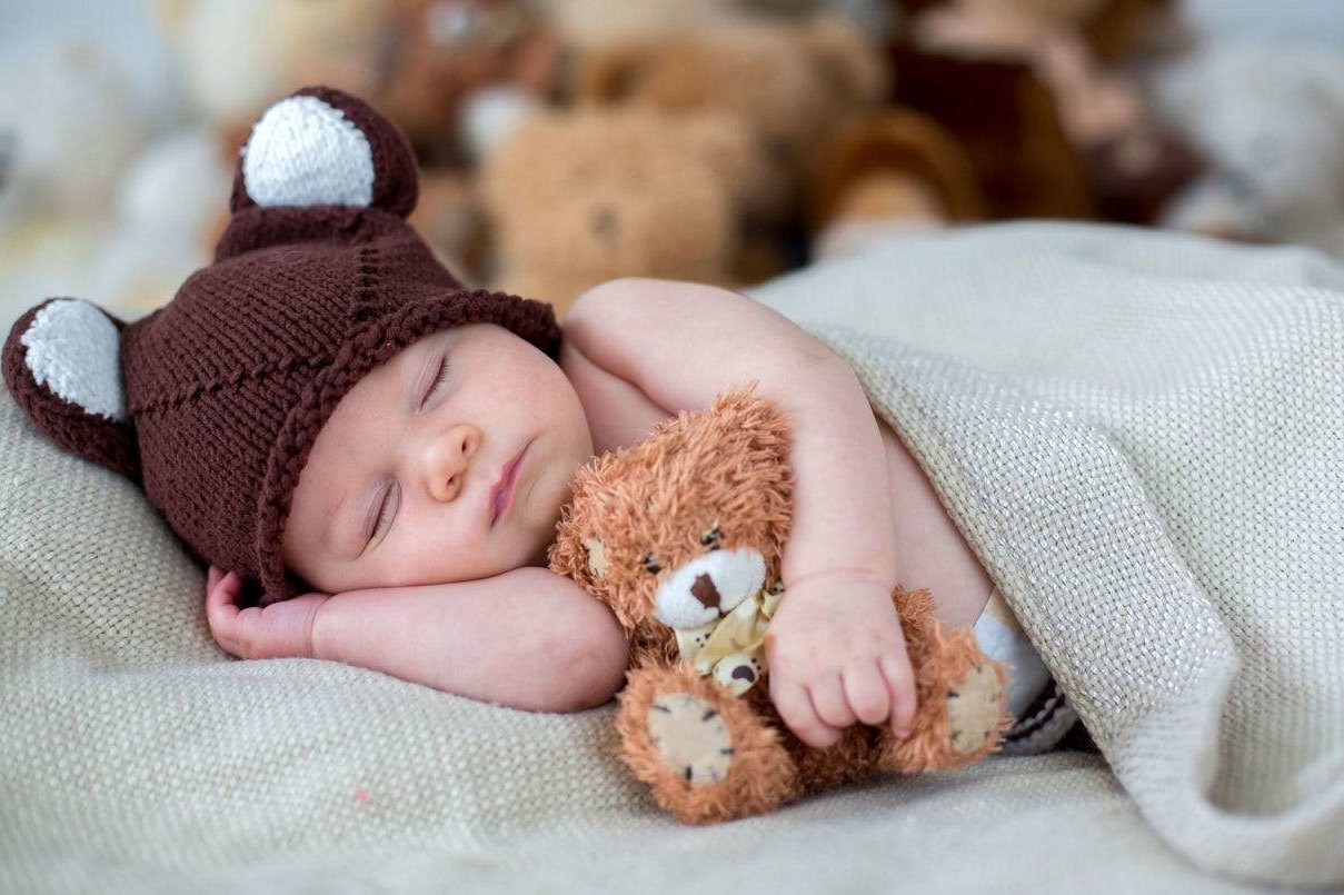 Little newborn baby boy sleeping with teddy bear at home in bed infant resting with toy
