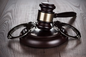 handcuffs-and-judge-gavel-on-brown-table-P9LWQWT-min-scaled