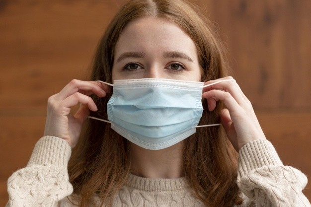front-view-woman-putting-medical-mask_23-2148802234