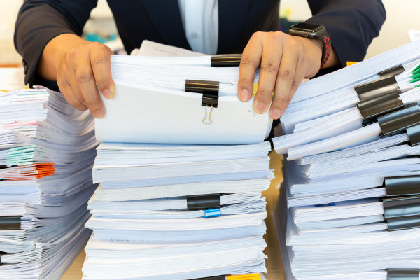 businessman-in-suit-look-through-pile-of-documents-in-office_42667-873