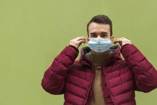 front-view-man-putting-medical-mask-with-copy-space_23-2148802219