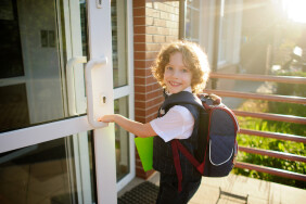 Little Kinky schoolboy opens a school door. The boy's pretty face. Behind the backpack, in the hands of bright green folder. Schoolboy looks into the camera and smiles.