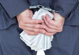 businessman in handcuffs holding bribe on white background
