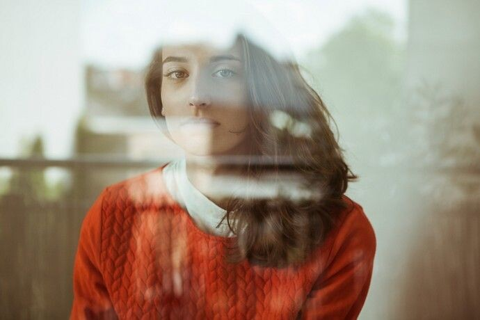 Portrait of serious young woman behind glass pane