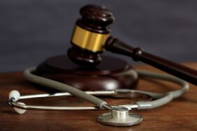 judge-gavel-and-a-stethoscope-on-a-wooden-desk-PVVCT33-min