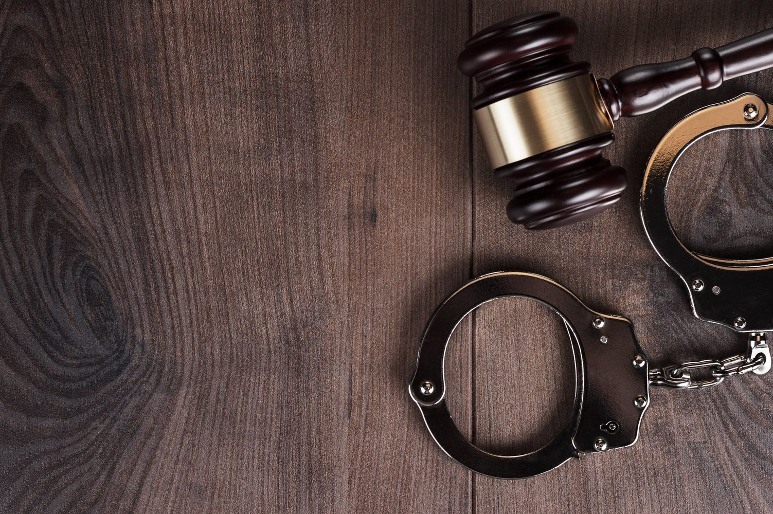 handcuffs-and-judge-gavel-on-wooden-background-PQKNDCW-min-1-scaled