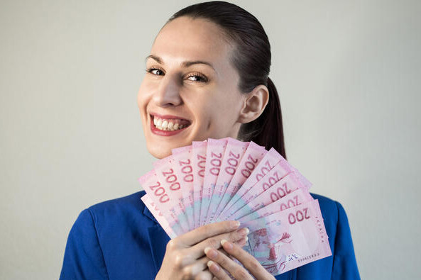 Young woman in classic blue jacket holding banknotes near face isolated on grey background.Portrait of a successful businesswoman in suit holding bunch of money banknotes and looking at camera