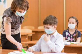 school kids and teacher with protection mask against flu virus at lesson